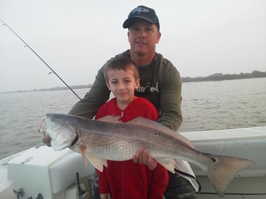Fishing charter capt. Greg Verm with child holding his catch